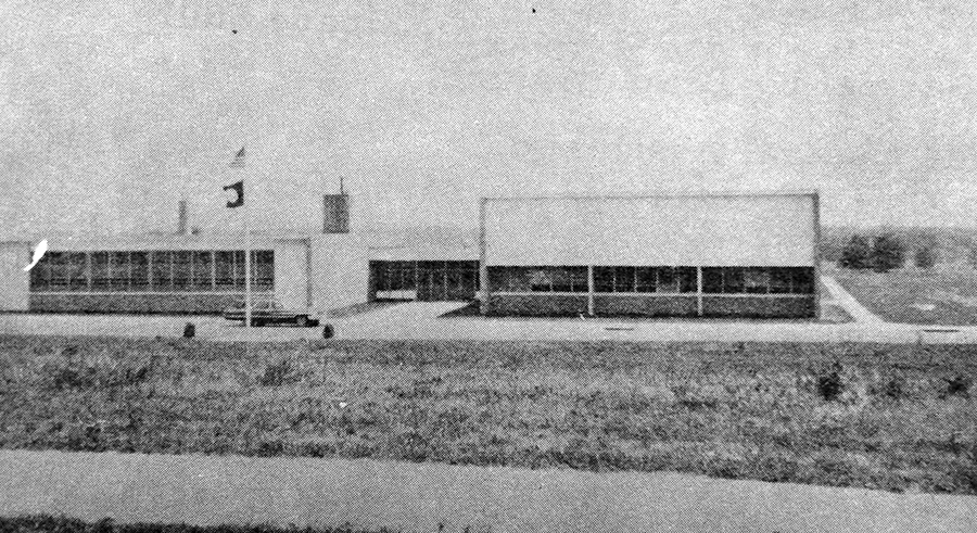 Black and white photograph of the main entrance to Hayfield Elementary School taken in 1967. The multi-purpose room and cafeteria are on the left, and the classroom wing and offices are on the right. A station wagon is parked in front of the building. A sidewalk runs down the side of the building where an addition will be constructed in 1972. Two small trees or shrubs have been planted near the flagpole.