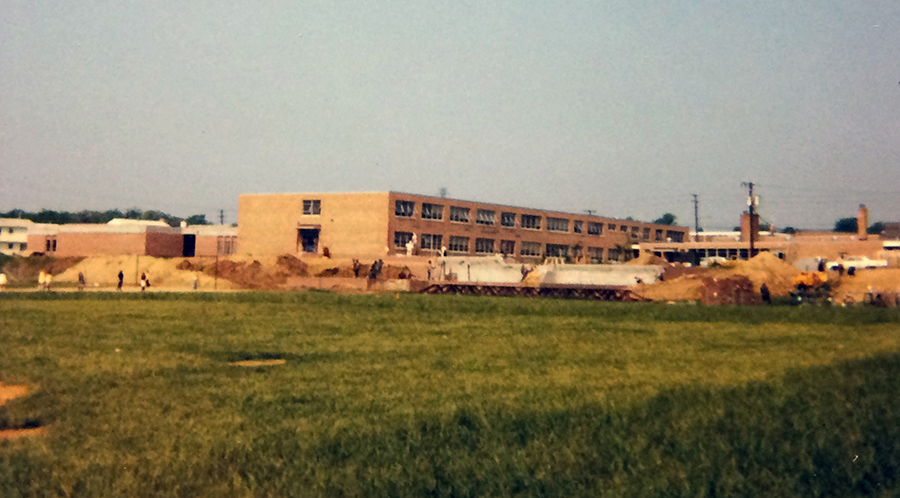 Color photograph of the exterior of Hayfield Elementary School taken from the playing fields behind the school. Construction work is in progress because there are large mounds of earth between the field and the school. The open classroom wing is complete, but the gymnasium and music room addition are not yet constructed.