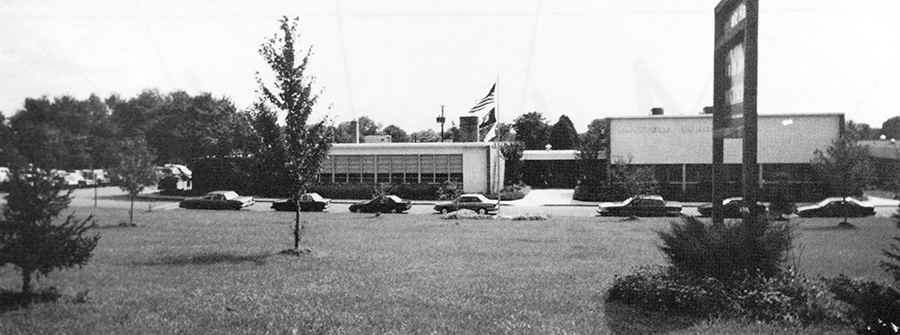 Black and white photograph of the front of Hayfield Elementary School from our 1993 to 1994 yearbook. The building was photographed from the sidewalk along Telegraph Road. A row of cars is parked in the bus loop in front of the school.