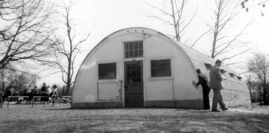 Black and white photograph taken in 1954 of a Quonset hut at Fairfax Elementary School. The building is a long semi-cylindrical structure with a door and three windows on one end and four windows along each side. The buildings were made out of metal and could be rapidly assembled and disassembled. Children can be seen to the left of the Quonset hut playing on the playground. Two men are examining the structure.
