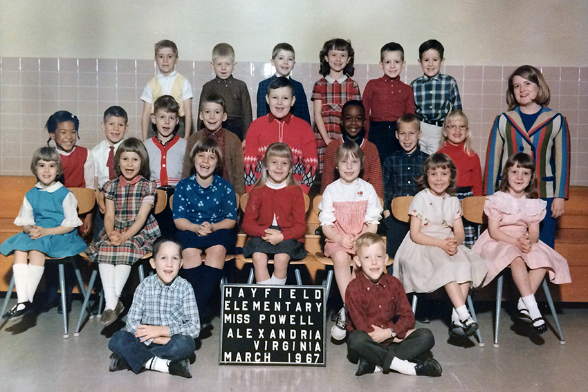 Color class photograph from the 1966 to 1967 school year. A sign indicates the teacher's name was Miss Powell and that the picture was taken in March 1967. 23 children are pictured, an even mix of boys and girls. Some are standing, others are seated. The girls are all wearing dresses or skirts and the boys are wearing button down shirts or sweaters. Miss Powell can be seen standing on the right. She has shoulder length blonde hair and is wearing a multi-colored vertical striped blazer and crew neck blue blouse.