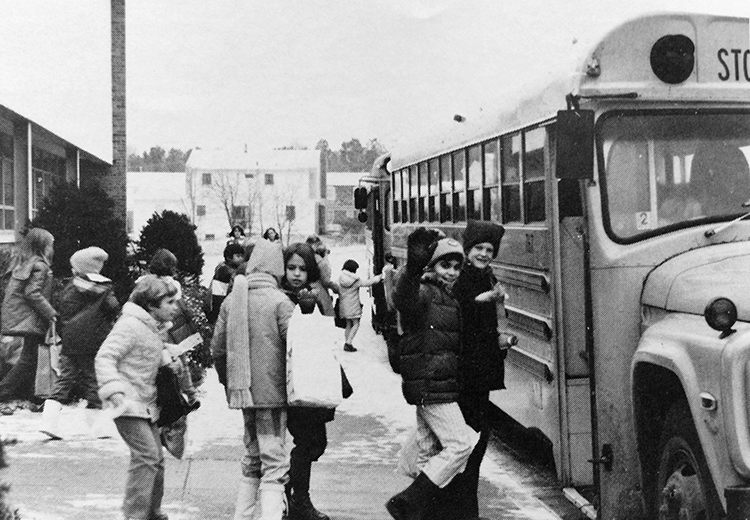 Black and white yearbook photograph taken in 1980 showing students at dismissal. It is wintertime and there is snow on the ground. The children are wearing heavy coats and are boarding school buses. One of the children is waving at the camera.